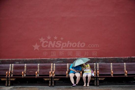 北京故宫游客雨中小憩