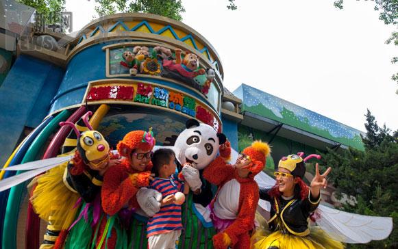"""5月22日,《动物总动员》演员身着戏服在门口与孩子一起玩耍。   当日,北京动物园和中国木偶剧院联手打造的""""动物城堡""""正式对外营业,中国木偶剧院专门为此项目创作的舞台剧《动物总动员》成为开场演出。""""动物城堡""""的前身是北京动物园内一处修建于上世纪50年代闲置已久的象舍,经过消防、疏散等多个环节的改造后,将变身为中国木偶艺术剧院驻场演出的场所。   新华社记者 张宇 摄"""